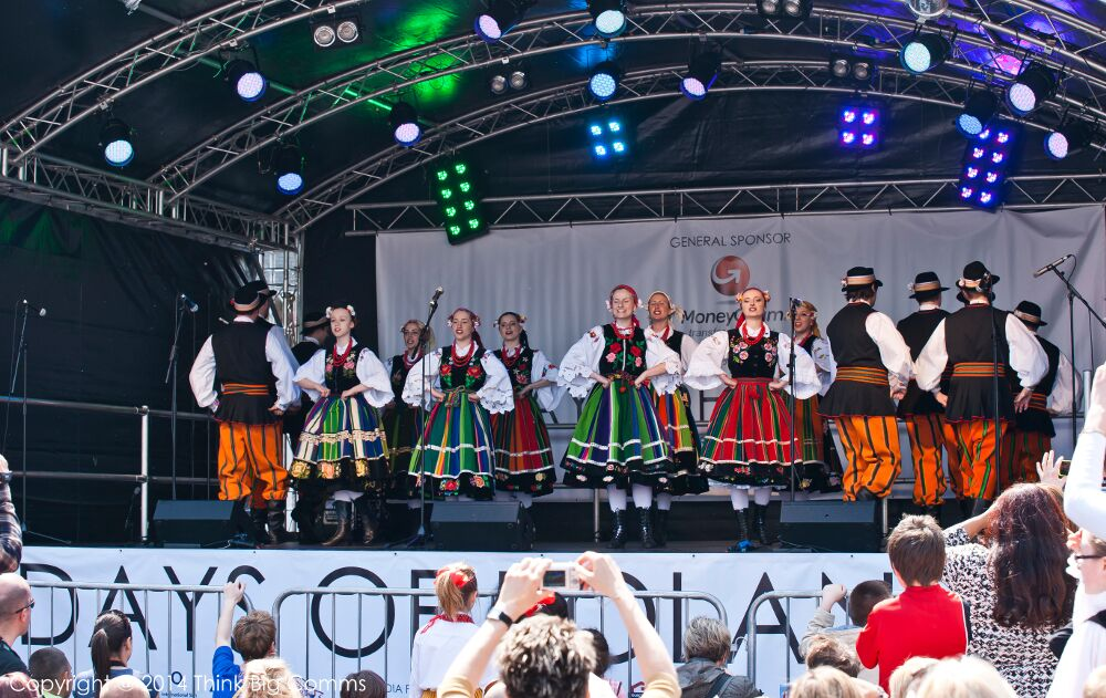 Couples in Polish national costumes dancing on the stage