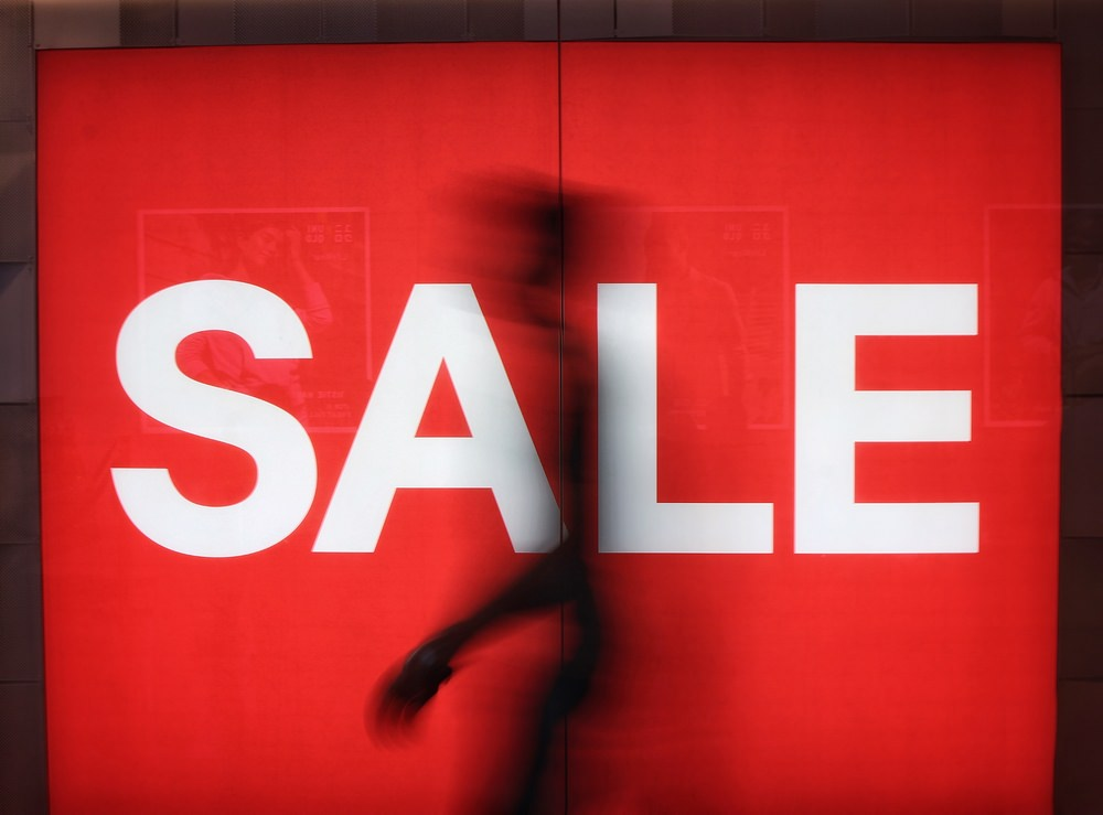 A person walking by a shop with a sale